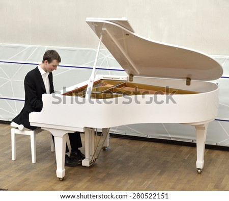 Beautiful and elegant young pianist plays white grand piano