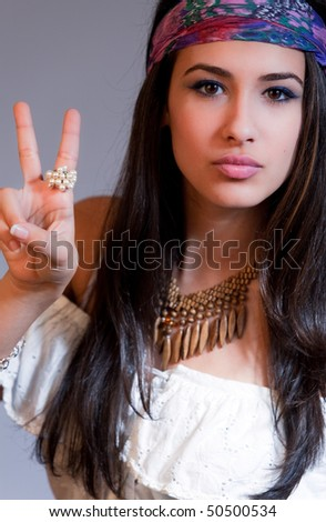 Beautiful and exotic young woman of multiple ethnicity waiving peace sign with 1960s wardrobe similar to a hippie.