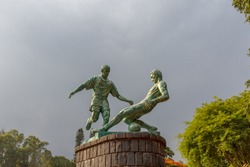 Beautiful and eye catching football players stone sculpture offers playing scene with dark sky in the background, with green trees adds beauty to the photograph salem tamil nadu india chennai