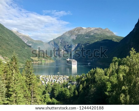 Beautiful and famous Geirangerfjord in Norway during summer. Cruiseship visiting Geiranger. Girl tourist hiking above the fjord.