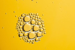 Beautiful and fantastic macro photo of water droplets in oil with a yellow background. Abstract art