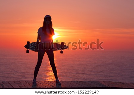 Beautiful and fashion young woman posing at teh sunset with a skateboard - stock photo