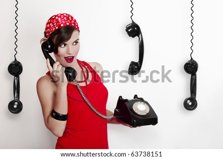 Beautiful and fashion young woman with a pin-up look. posing with a vintage phone
