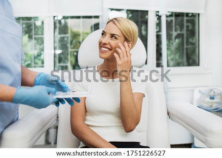 Beautiful and happy blonde woman at beauty medical clinic. She is sitting and talking with female doctor about face esthetics treatment. Photo stock ©