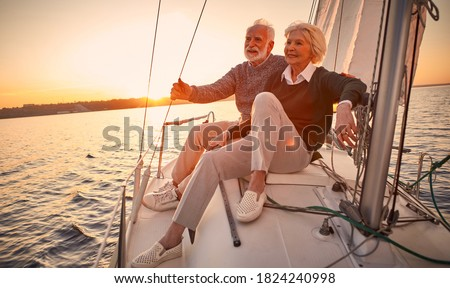 Beautiful and happy senior couple in love sitting on the side of sailboat or yacht deck floating in sea at sunset and enjoying amazing view, sailing together