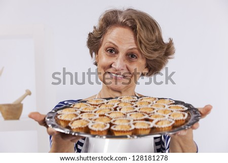 Beautiful and happy senior woman cooking at her kitchen showing their cookies