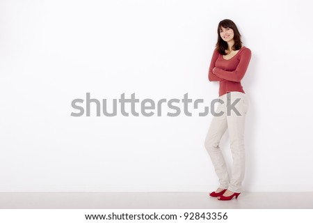 Beautiful and happy woman, against a white wall with copyspace on the left side.