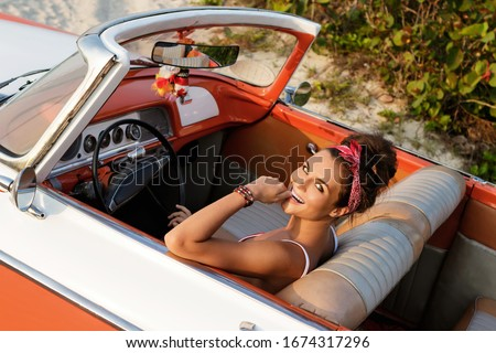 Beautiful and happy woman is wearing bandana driving retro cabriolet car