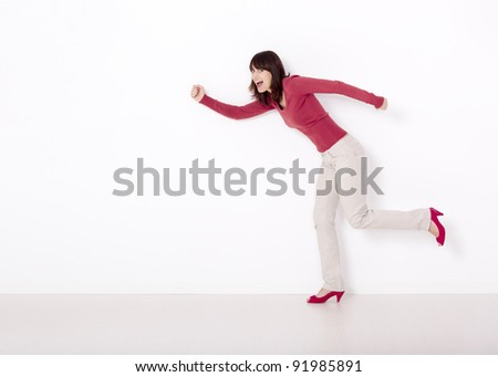 Beautiful and happy woman simulating she's running against a white wall