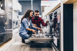 Beautiful and happy young couple buying dishwasher in modern appliances store.