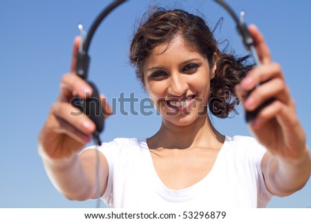 Beautiful and happy young girl holding headphones