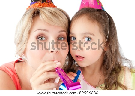 beautiful and happy young mother and small daughter celebrating birthday. Both wearing birthday hats and looking into the camera. Studio shot, isolated on white background