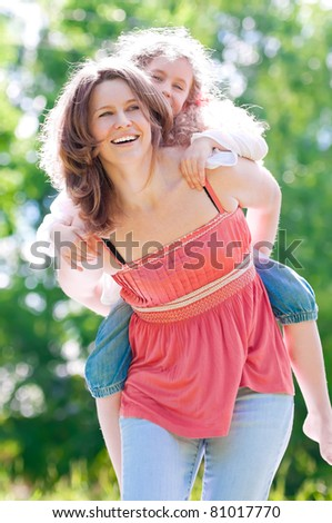 Beautiful and happy young mother giving piggyback ride to her daughter. Both smiling. Summer park in background.
