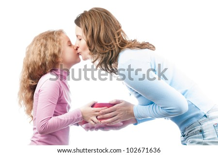 Beautiful and happy young mother giving present to her small daughter and kissing her. Isolated on white background.