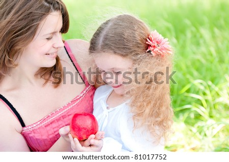Beautiful and  happy young mother holding apple in her hand together with her small daughter. Summer park in background