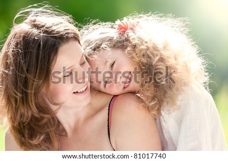 Beautiful and  happy young mother with her daughter on her shoulder. Both smiling, summer park in background