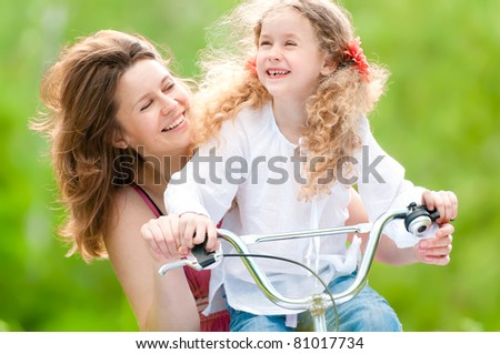 Beautiful and happy young on bicycle with her daughter. Both smiling, summer park in background.