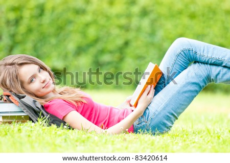 beautiful and happy young student girl lying on grass with opened book, smiling and looking into the camera. Pile of books under her head. Summer or spring green park in background