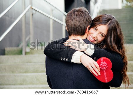Beautiful and happy young woman in love hugging her boyfriend holding a red heart shaped gift box #760416067