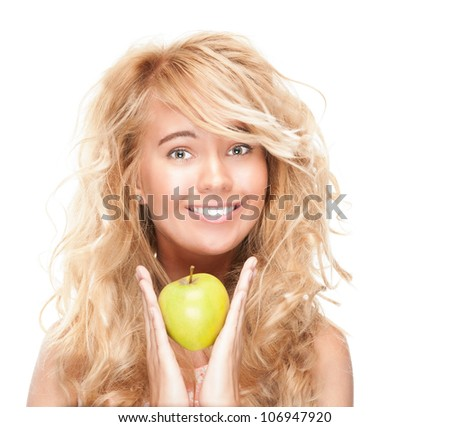 Beautiful and happy young woman isolated on white background. Looking into the camera and smiling. Holding the apple in her hands at her face, perfect white teeth.