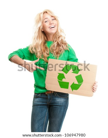 Beautiful and happy young woman isolated on white background. Smiling and looking into the camera. Piece of cardboard in her hand with green recycle symbol. Pointing to the cardboard with her hand.