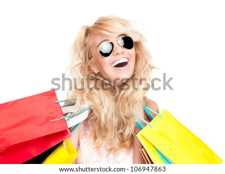 Beautiful and happy young woman standing isolated on white background with shopping bags in her hands. Looking into the camera and laughing. Wearing sunglasses.