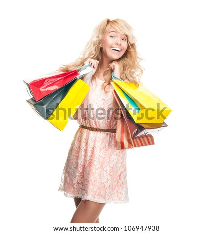 Beautiful and happy young woman standing isolated on white background with shopping bags in her hands. Looking into the camera and laughing.