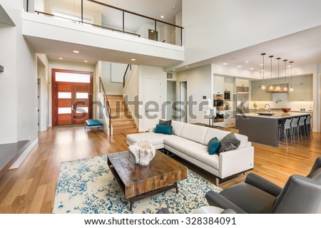 Beautiful and large living room interior with hardwood floors and vaulted ceiling in new luxury home. View of Kitchen, entryway, and second story loft style area #328384091