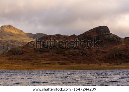Beautiful and moody morning fall light at Blea Tarn in the English Lake District with views of the Langdale Pikes, and Side Pike during autumn. #1547244239