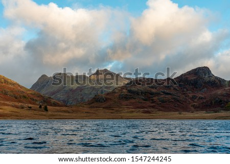 Beautiful and moody morning fall light at Blea Tarn in the English Lake District with views of the Langdale Pikes, and Side Pike during autumn. #1547244245