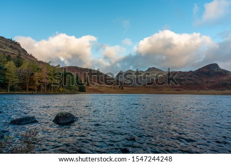 Beautiful and moody morning fall light at Blea Tarn in the English Lake District with views of the Langdale Pikes, and Side Pike during autumn. #1547244248