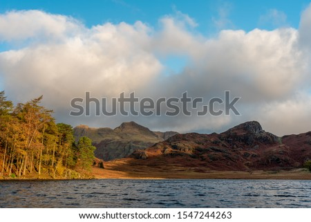 Beautiful and moody morning fall light at Blea Tarn in the English Lake District with views of the Langdale Pikes, and Side Pike during autumn. #1547244263