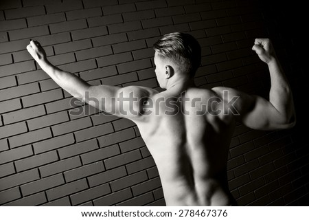 Beautiful and muscular black man\'s back in dark background