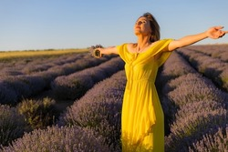 Beautiful and pretty young woman in a yellow dress relaxes and enjoys a walk in the lavender field at sunset, toned