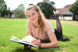 Beautiful and relaxed female student lying on the grass in a park and scrolling through her study book
