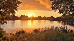 Beautiful and romantic sunset at a lake in yellow and orange colors