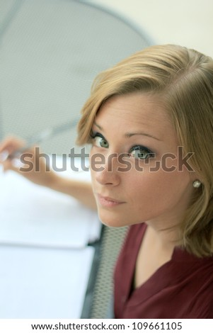Beautiful and Serious Business Woman Looking At Camera While Writing