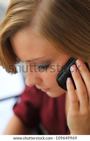 Beautiful and Serious Business Woman Talking on the Phone While Looking Down