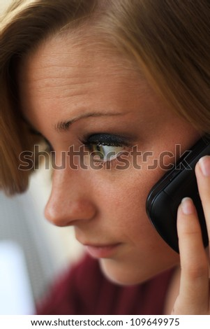 Beautiful and Serious Business Woman Talking on the Phone While Looking Straight Ahead