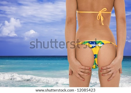 Beautiful and sexy caucasian woman in her early 20s posing in a Brazilian thong bikini with the turquoise waters and white sand beaches of Rio de Janeiro Brazil