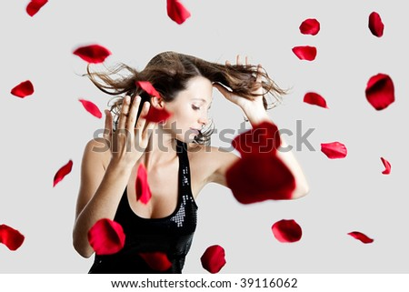 Beautiful and sexy fashion model posing with rose petals