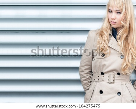 Beautiful and sexy young girl posing outside against garage door. Looking into the camera. Blond long hair and fashion look.