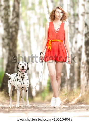 Beautiful and sexy young woman in red dress with dalmatian dog in summer forest.