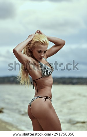Beautiful and sporty body of sexy woman. Beautiful athletic girl on the beach. Bodybuilding.
