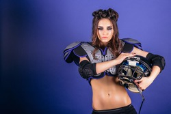 Beautiful and sporty brunette in the shape of an American football player with a ball on a blue background