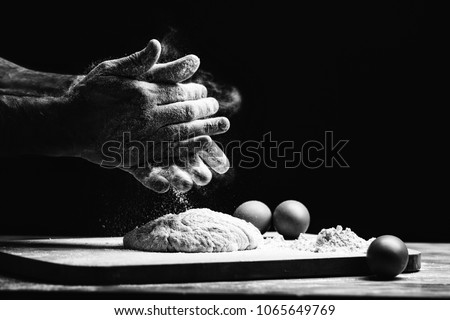 Beautiful and strong men's hands knead the dough from which they will then make bread, pasta or pizza. A cloud of flour flies around like dust. Next to the chicken egg. The background is dark.
