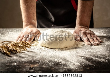 Beautiful and strong men's hands knead the dough from which they will then make bread, pasta or pizza. A cloud of flour flies around like dust. Food concept.