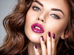 Beautiful and stunning woman with bright purple lipstick on lips and fingernails.  Young caucasian gorgeous adult girl. Model. Closeup woman's portrait. Vivid make-up. Sexy female.