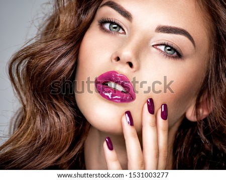 Beautiful and stunning woman with bright purple lipstick on lips and fingernails.  Young caucasian gorgeous adult girl. Model. Closeup woman