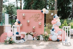 Beautiful and stylish location for wedding photos decorated with balloons, flowers and original globes. Photo zone on pink background in the open air
